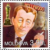 A stamp of an man holding a cigarette. Near him an Academy Award, a woman and some white capital letters are visible.
