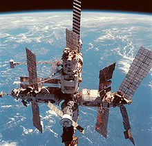 A cluster of cylindrical modules with projecting feathery solar arrays, with Earth's horizon visible in the background.