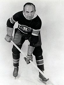 An ice hockey player leans forward with his stick. He has a round face with one eyebrow raised and a bare head with a receding hairline. He wears skates, gauntlets, and a sweater with a stylized