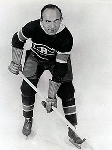 "An ice hockey player leans forward with his stick. He has a round face with one eyebrow raised and a bare head with a receding hairline. He wears skates, gauntlets, and a sweater with a stylized ""C"" around a smaller ""H""."