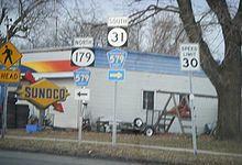 Two adjacent road signs at a T-intersection with the left sign reading north Route 179 Hunterdon County Route 579 with a left arrow and the left sign reading south Route 31 Hunterdon County Route 579 with a right arrow. A Sunoco gas station lies in the background