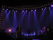 A rock band performing live on-stage. To the left, one man sings into a microphone and another man plays drums. In the centre, one man plays guitar and another man plays bass. To the right, one man plays a violin and another man plays drums.