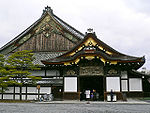 A small wooden structure with a hip-and-gable roof, white walls and metal ornaments on the gable is located in front of a large building with hip-and-gable roof, white walls and chrysanthemum motifs on the gable.