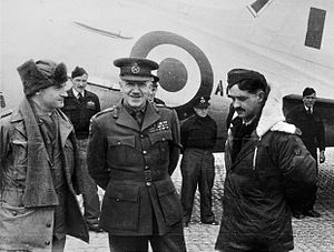 Six men in military dress standing in front of an aircraft
