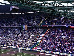 Tifoserie avverse durante un derby della Old Firm: a sinistra in verde-bianco-oro i tifosi del Celtic con esposte bandiere irlandesi, a destra i sostenitori dei Rangers coi colori tipici della propria squadra e britannici, blu-rosso-bianco