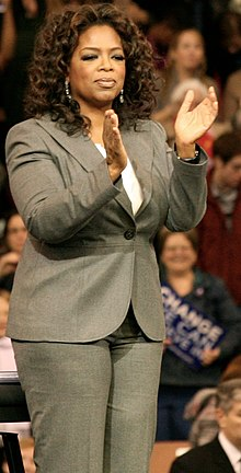 Picture of a woman in a suit clapping.