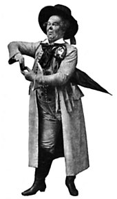 Actor in exaggerated stage pose, wearing a wide-brimmed hat and long heavy coat, carrying an umbrella