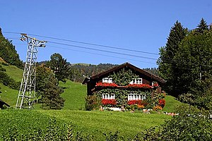 Illgau - Farm house in Illgau, with a tower of the aerial tramway Illgau - St.Karl
