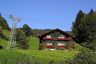 Illgau - Farm house in Illgau, with a tower of the aerial tramway Illgau - St.Karl