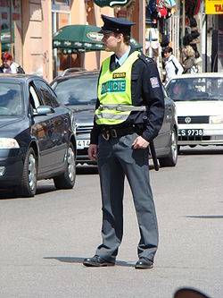 Policeman standing in street, wearing safety vest