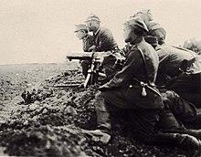 Grupa piechoty leży lub klęczy w płytkim okopie. Na pierwszym planie trójosobowa obsługa karabinu maszynowego, za nimi widocznych dwóch oficerów klęczących o krok przed okopem, widocznych także kilka karabinów wycelowanych z okopu w stronę pola widocznego po lewej stronie kadru. Trzymających je żołnierzy zasłania obsługa kaemu na pierwszym planie.