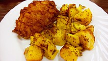 A Pozharsky cutlet with cubed potatoes on a plate
