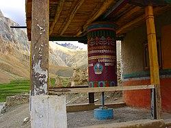 A prayer wheel with chorten in background.