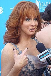 A woman with long red hair wearing a grey dress, talking into a microphone