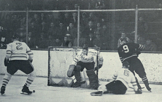 Red Berenson - Berenson (No. 9) cuts behind the net against Colorado College 1961
