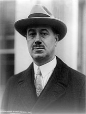 Black and white photograph of McCormick wearing a fedora and overcoat.