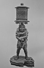 Ryūtōki. Front view of a stocky statue with a demon face. He is balancing a lantern on his head. He is grabbing his right wrist with the left hand. Black and white photograph.