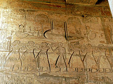 Relief showing rows of men carrying poles that support a model boat.
