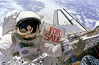 "Astronaut Dale Gardner holding a ""For Sale"" sign"