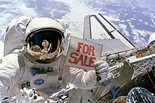 "Mission Specialist Dale Gardner holds up a ""For Sale"" sign, referring to the malfunctioning Palapa B2 and Westar 6 satellites."