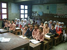 School children in Rhbat, Nagar sit in classroom learning. The boys are in the front with the girls behind them.