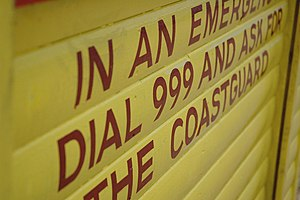 999 (emergency telephone number) - A sign on a beach in Whitstable, United Kingdom, advising readers to dial 999 in the event of an emergency.