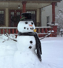 Photograph of a classic-style snowman in scarf and hat with pipe and carrot nose, in Winona Lake, Indiana, USA