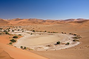 Namib - Sossusvlei, one of the Namib's major tourist attractions, is a salt and clay pan surrounded by large dunes. The flats pictured here were caused by the Tsauchab stream after summer rains