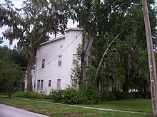 a two story square building partially obscured by oak trees