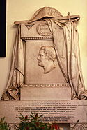 Photograph of a marble memorial carved with the image of James Brisbane in profile, carved cloth over the top and text on a panel beneath