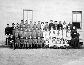 Posed, group photo of students and teachers, dressed in black and white, outside Middlechurch, Manitoba's St. Paul's Indian Industrial School