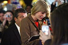 Swift is seen signing autographs. She is wearing a brown trench coat and red lipstick
