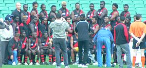 """Tiwi Bombers Football Club - The Tiwi Bombers team line-up for a historic match against Rumbalara at the Melbourne Cricket Ground as a curtain raiser to the """"Dreamtime at the 'G"""" game. The Bombers defeated their Victorian opponents by a massive margin, posting a near ground record score."""
