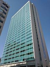Torre com fachada de vidro azul e laterais de concreto branco
