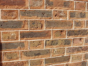 Tuckpointing - Here red mortar is used. The white fillets are laid out at regular spacing, which does not always coincide with the rough spacing of the joints.