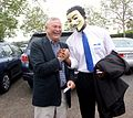 U.S. Congressman Dana Rohrabacher shakes hands with a supporter wearing Guy Fawkes mask.jpg