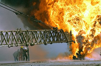 Oil well fire - Kuwaiti firefighters fight to secure a burning oil well in the Iraqi Rumaila oilfields in 2003.