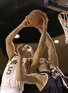 US Navy 031124-N-9693M-003 Navy sophomore guard David Hooper pulls down a rebound over Belmont senior guard Steve Drabyn during the Midshipmen's home opener at the U.S. Naval Academy.jpg
