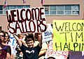 US Navy 050908-N-0653J-002 A family member holds-up a welcome home sign as he welcomes home his cousin who is assigned to the Los Angeles-class attack submarine USS Augusta (SSN 710).jpg