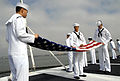 US Navy 070402-N-1205S-192 Aviation Support Equipment Technician 3rd Class Danny Ly, Storekeeper Seaman Joe Jackson and Electronics Technician Timothy Swartz fold the American flag on the flight deck aboard nuclear-powered airc.jpg