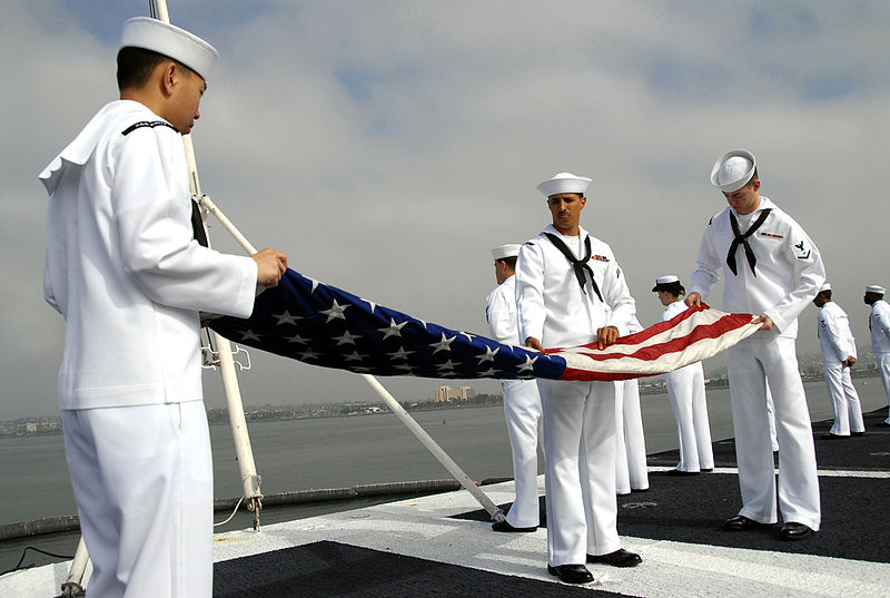 Navy caption: SAN DIEGO (April 2, 2007) - Aviation Support Equipment Technician 3rd Class Danny Ly, Storekeeper Seaman Joe Jackson and Electronics Technician Timothy Swartz fold the American flag on the flight deck aboard nuclear-powered aircraft carrier USS Nimitz (CVN 68). Nimitz Carrier Strike Group (CSG), embarked Carrier Air Wing (CVW) 11 and Destroyer Squadron Group (DESRON) 23 are deploying to support operations in U.S. Central Command area of responsibility. U.S. Navy photo by Mass Communication Specialist 2nd Class Jeremiah Sholtis (RELEASED) - Wikimedia image