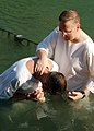 US Navy 080915-N-4345B-003 Cmdr. Jonathan Smith, command chaplain for the amphibious assault ship USS Iwo Jima (LHD 7), baptizes Senior Chief Hospital Corpsman Brian Wenzel in the Jordan River.jpg