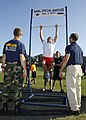 US Navy 091003-N-5366K-118 Capt. Adam Curtis and Cmdr. Brian Casson, assigned to Naval Special Warfare (NSW) Command help to motivate a student during the Navy SEAL Fitness Challenge held at Grimsley High School.jpg