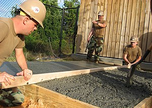 Screed - US Navy Seabees use a screed (board) to screed (verb) wet concrete. The form-work acts as screed rails.