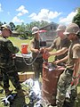 US Navy 100823-N-5390M-005 Seabees assigned to Amphibious Construction Battalion (ACB) 1, based in San Diego, hand pump gas into a container to be used for generators at the Vunamami Farmer's Training Center engineering site.jpg