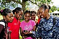 US Navy 110502-F-HS649-178 Hospital Corpsman 1st Class Cassandra Townsend shows students a music video on her cell phone at Matevulu College during.jpg