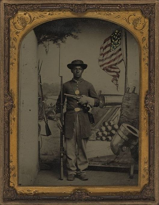 Unidentified African American Union soldier with a rifle and revolver in front of painted backdrop showing weapons and American flag at Benton Barracks, Saint Louis, Missouri LOC 5229147154 (cropped)