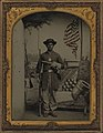 Unidentified African American Union soldier with a rifle and revolver in front of painted backdrop showing weapons and American flag at Benton Barracks, Saint Louis, Missouri LOC 5229147154 (cropped).jpg