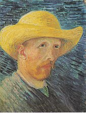 A man with a red beard in a straw hat looks to his right