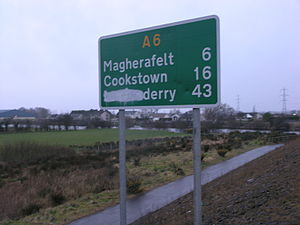 Derry - Road sign in Northern Ireland with the reference to London obscured